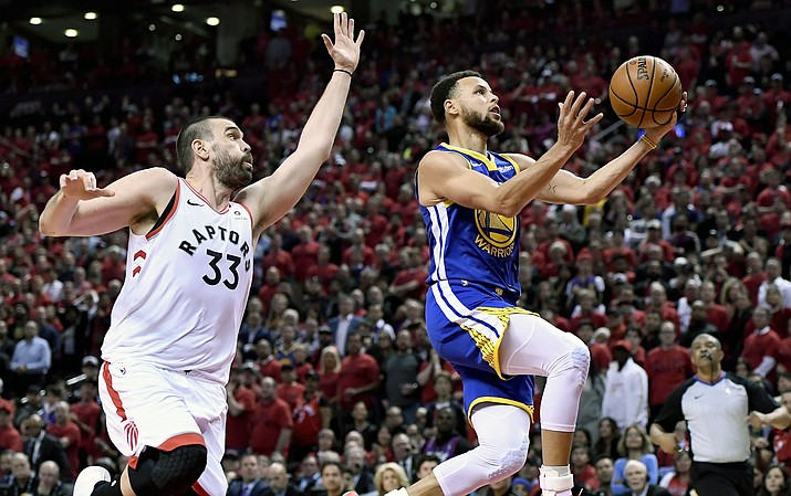 Golden State Warriors guard Stephen Curry (30) drives to the net as Toronto Raptors center Marc Gasol (33) looks on during the first half of Game 2 of the NBA Finals, Sunday, June 2, 2019, in Toronto. (Frank Gunn/The Canadian Press via AP)