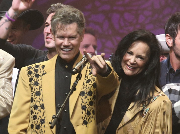 "This Feb. 8, 2017 file photo shows country singer Randy Travis, left, and his wife Mary Travis at the ""1 Night. 1 Place. 1 Time.: A Heroes and Friends Tribute to Randy Travis"" in Nashville, Tenn. Travis, who survived a near fatal stroke in 2013 that left him with a limited ability to speak, released his first memoir, ""Forever and Ever, Amen: A Memoir of Music, Faith and Braving the Storms of Life,"" chronicling his rise to fame. (Laura Roberts/Invision/AP, File)"