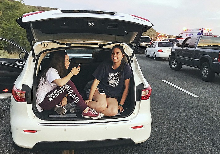 In this May 14, 2017, photo, Brian Swanton's daughters Emma Swanton, 13, left, and Abigail Swanton pass the time after a pair of collisions brought traffic to a standstill for some five hours on Interstate 17 near Black Canyon City. Arizona's next state budget will help pay for building additional lanes along 23 miles (37 kilometers) of Interstate 17 north of the Phoenix area in two stretches where traffic can be clogged, particularly on summer and holiday weekends and after wrecks. (Brian Swanton via AP)