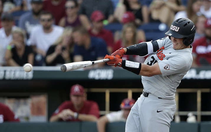 In this June 28, 2018, photo, Oregon State's Adley Rutschman hits an RBI single to score Cadyn Grenier during the third inning of Game 3 against Arkansas in the NCAA College World Series finals, in Omaha, Neb. The Baltimore Orioles led off the Major League Baseball Draft for the first time in 30 years and Oregon State catcher Adley Rutschman was a heavy favorite to be selected No. 1 on Monday night, June 3, 2019. (Nati Harnik/AP, File)