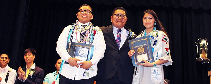 Hopi Vice Chairman Clark Tenakhongva gives citizenship awards to Arion Sahneyah and Evonne Sidney at the Hopi Jr. High Promotion May 22. (Stan Bindell/NHO)