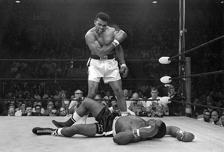 Muhammad Ali stands over Sonny Liston after knocking Liston down during their' heavyweight championship bout in Lewiston, Maine. (AP Photo/John Rooney, File)