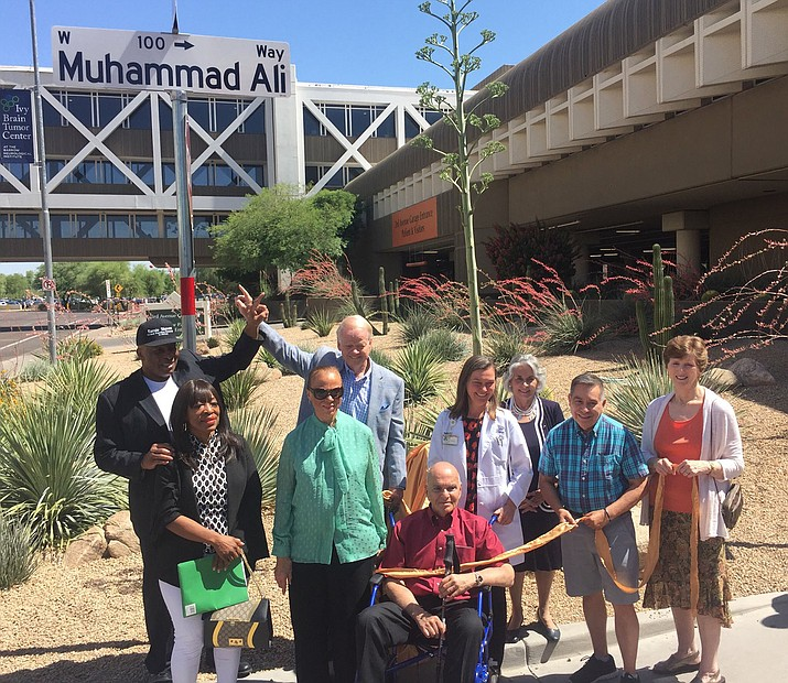 "A small group, including his widow, Yolanda ""Lonnie"" Ali, in green, pose under the newly created ""Muhammad Ali Way."" (Photo by Jacob Rosenfarb/Cronkite News)"