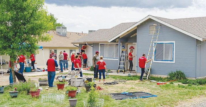 Volunteers work to complete the exterior paint job on a Prescott Valley home before the rains came May 9 on Keller Williams' national Red Day event. (Matt Hinshaw, Keller Williams/Courtesy)