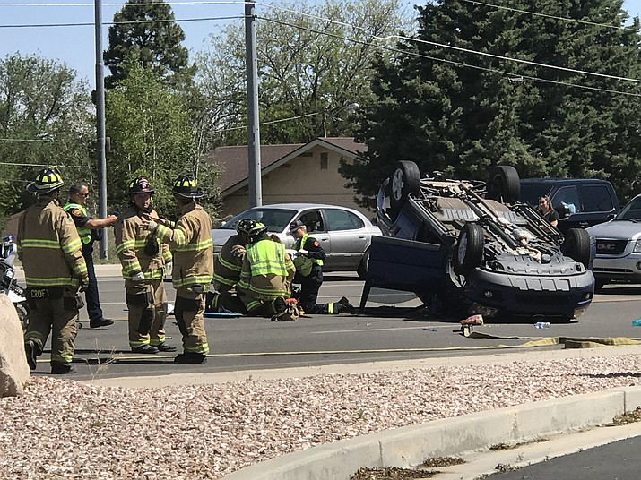Emergency responders treat a woman whose car rolled on Willow Creek Road Tuesday morning, June 4. (Les Stukenberg/Courier)