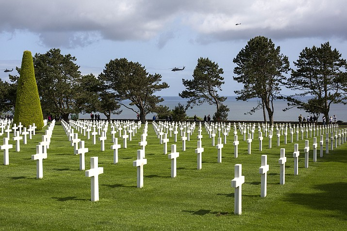 People visit as helicopters pass overhead Monday, June 3, 2019. at the Normandy American Cemetery in Colleville-sur-Mer, Normandy, France. (Rafael Yaghobzadeh/AP)