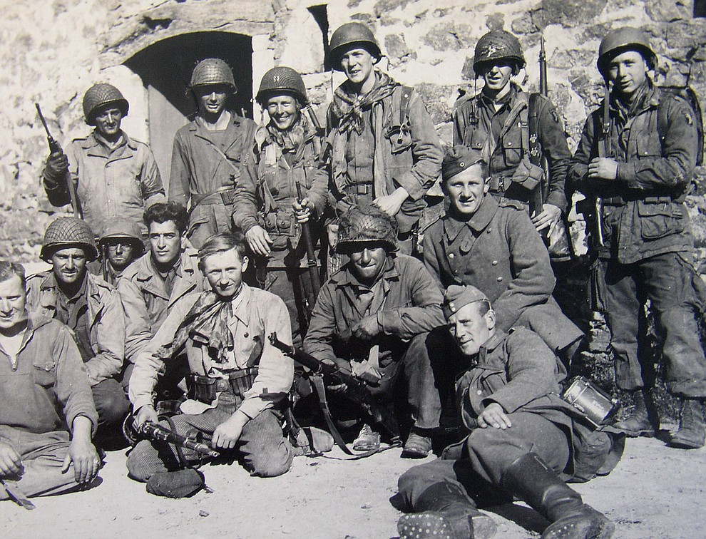 Infantry soldiers on the left, paratroopers back row center to right, a French resistance member kneeling front row and two German prisoners of war posing for a photo that is on display in a French museum. (Bill Morrison/Courtesy photo)