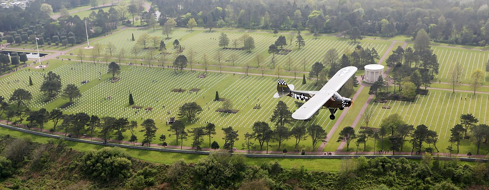 A Piper Cub with French Resistance hero Roland LePers flies over the cemetery above Omaha Beach during a 2009 tour of the Normandie region of France. (Bill Morrison/Courtesy photo)