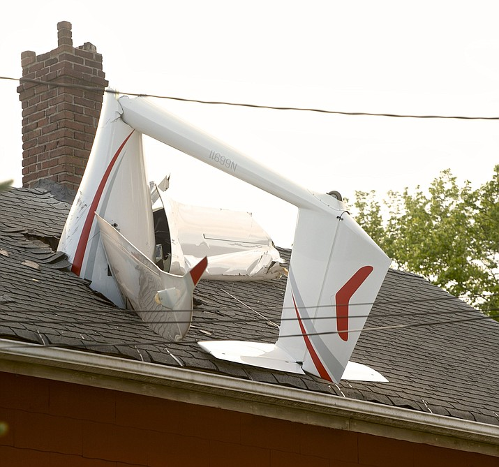 In this Tuesday evening, June 4, 2019 photo, a glider, flown by a local business owner, crashed into a house on Golden Hill Avenue while making its approach to Danbury Airport, in Danbury, Conn. Officials say the pilot sustained minor injuries. (H John Voorhees III/Hearst Connecticut Media via AP)