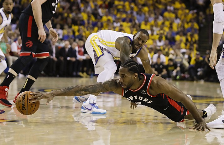 Toronto Raptors forward Kawhi Leonard, foreground, reaches for the ball in front of Golden State Warriors forward Andre Iguodala during the first half of Game 3 of the NBA Finals in Oakland, Calif., Wednesday, June 5, 2019. (Ben Margot/AP)
