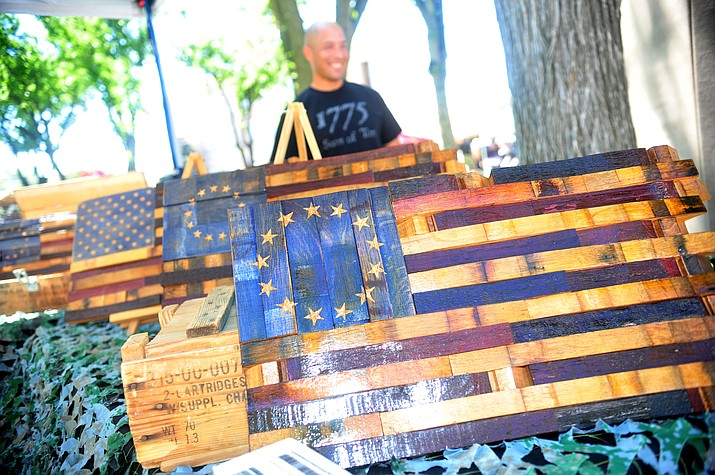 Alberto Martinez shows off some of his flag themed woodwork at Vintage Honor during the 2018 Territorial Days Arts and Crafts Show at the courthouse plaza. This year's event is from 9 a.m. to 5 p.m. Saturday, June 8, and 9 a.m. to 4 p.m. Sunday, June 9. (Les Stukenberg/Courier, file)