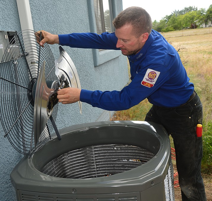 Rob Kunzmann of Comfort Pro Heating and Cooling checks the outdoor condensing unit at a Chino Valley residence Wednesday, June 5. (Les Stukenberg/Courier)