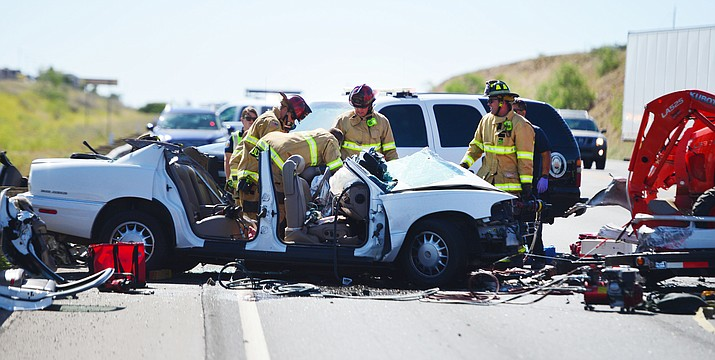 Emergency personnel try to free a victim trapped in her car after a trailer came unhitched and collided head-on with her car on Highway 69 at Mendecino in Prescott Valley Friday, June 7, 2019. (Les Stukenberg/Courier)