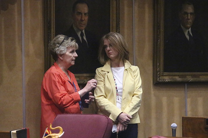 Republican Sens. Kate Brophy McGee, left, and Heather Carter, confer May 10, 2019, on the state Senate floor in Phoenix. Brophy McGee and Carter were responsible for the defeating a bill setting up a program to dissuade women from seeking abortions pushed by Cathi Herrod, who leads the powerful social conservative group Center for Arizona Policy. (Bob Christie/AP, file)