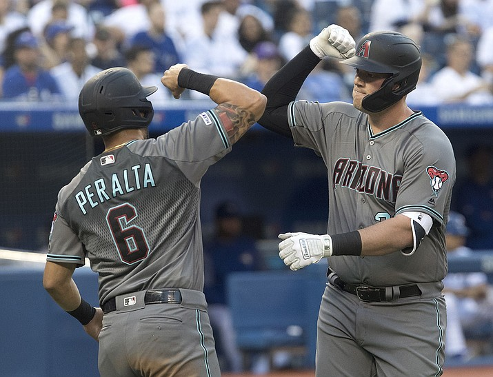 Arizona Diamondbacks' Kevin Cron, right, is greeted at home plate by David Peralta  after hitting a three-run home run against the Toronto Blue Jays in the fourth inning Friday, June 7, 2019, in Toronto. (Fred Thornhill/The Canadian Press via AP)