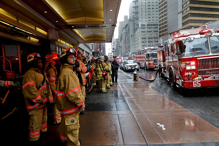 Firefighters respond to the scene where a helicopter crash-landed on the roof of a midtown Manhattan skyscraper, Monday, June 10, 2019, in New York.  (Mark Lennihan/AP)