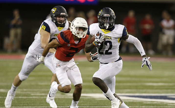 Northern Arizona running back Joe Logan (22) rushes for a first down against Arizona during the first half of an NCAA game, Saturday, Sept. 2, 2017, in Tucson, Ariz.  NAU has added a non-conference game against the University of Arizona for the 2027 season in an effort to continue the in-state rivalry. (Rick Scuter/AP, file)