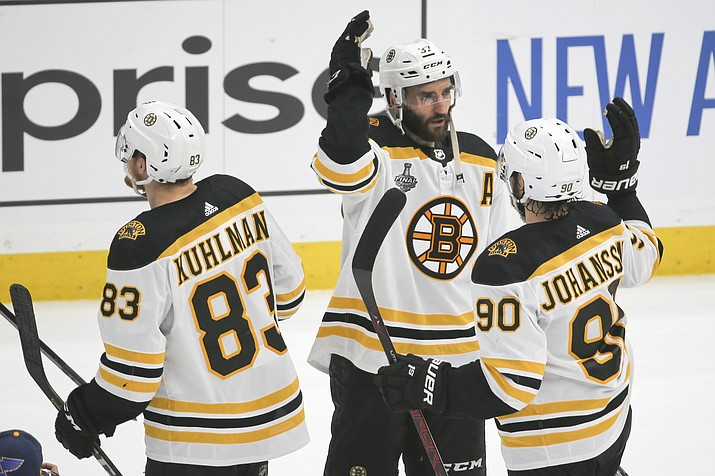 Boston Bruins center Patrice Bergeron (37) celebrates with Marcus Johansson (90) and Karson Kuhlman (83) after the Bruins beat the St. Louis Blues in Game 6 of the NHL Stanley Cup Final Sunday, June 9, 2019, in St. Louis. The Bruins won 5-1 to even the series 3-3. (Scott Kane/AP)