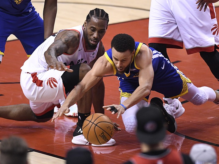 Toronto Raptors forward Kawhi Leonard (2) and Golden State Warriors guard Stephen Curry (30) vie for the ball during Game 5 of the NBA Finals in Toronto, Monday, June 10, 2019. (Frank Gunn/The Canadian Press via AP)