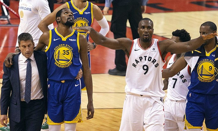 Golden State's Kevin Durant (35) walks off the court after sustaining an injury as Toronto's Serge Ibaka (9) gestures to the crowd during Game 5 of the NBA Finals in Toronto on Monday, June 10, 2019. (Chris Young/The Canadian Press via AP)