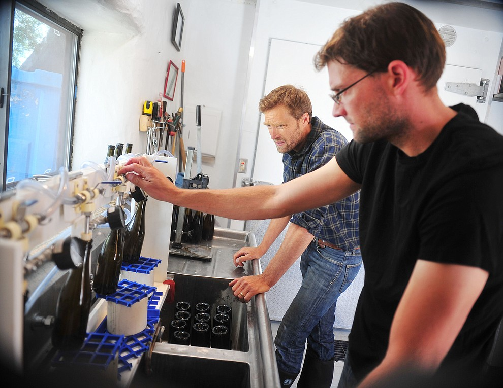 Cody and Kanin Tieney bottle some of their hard cider at the Stoic Cider orchard and bottling facility Tuesday, May 29 in Williamson Valley northwest of Prescott. (Les Stukenberg/Courier)