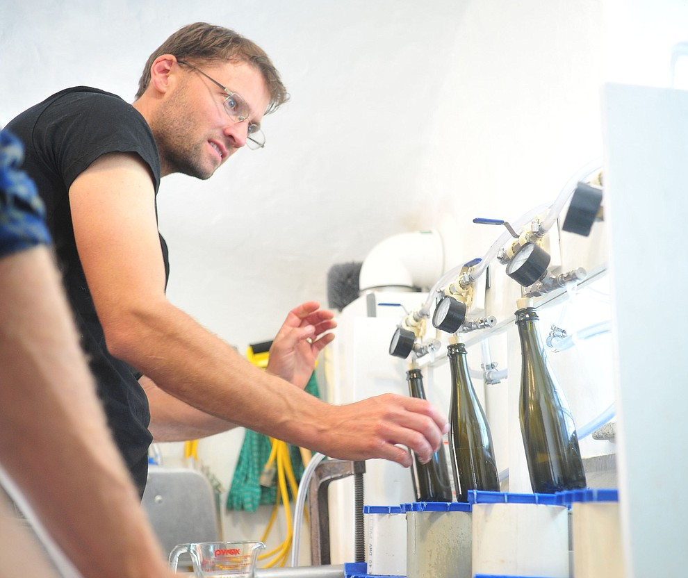 Cody Routson fills bottles at the Stoic Cider orchard and bottling facility Tuesday, May 29 in Williamson Valley northwest of Prescott. (Les Stukenberg/Courier)