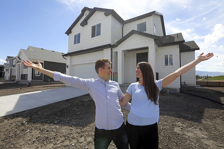 In this April 27, 2019, photo, Andy and Stacie Proctor stand in front of their new home in Vineyard, Utah. For some millennials looking to buy their first home, the hunt feels like a race against the clock. The Proctors ultimately made a successful offer on a three-bedroom house for $438,000 in Vineyard. (Rick Bowmer/AP)