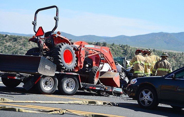 Emergency personnel try to free a victim trapped in her car after a trailer came unhitched and collided head-on with her car on Highway 69 at Mendecino Drive in Prescott Valley Friday, June 7, 2019. (Les Stukenberg/Courier)