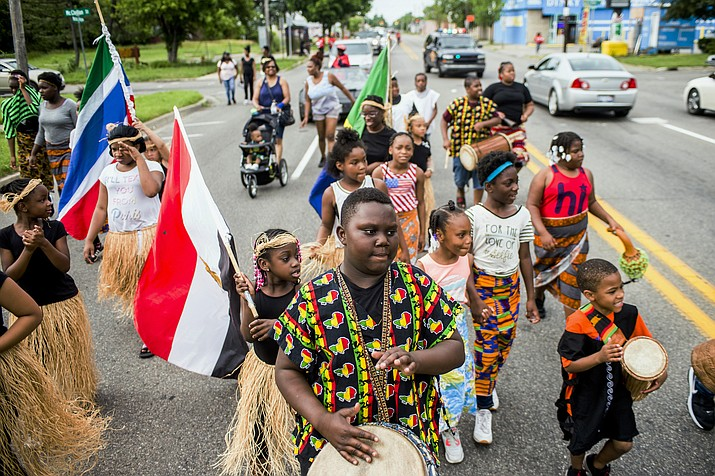 Zebiyan Fields, 11, at center, drums alongside more than 20 kids at the front of the Juneteenth parade June 19, 2018, in Flint, Mich. Juneteenth celebration started with the freed slaves of Galveston, Texas. Although the Emancipation Proclamation freed the slaves in the South in 1863, it could not be enforced in many places until after the end of the Civil War in 1865. (Jake May/The Flint Journal via AP, File)