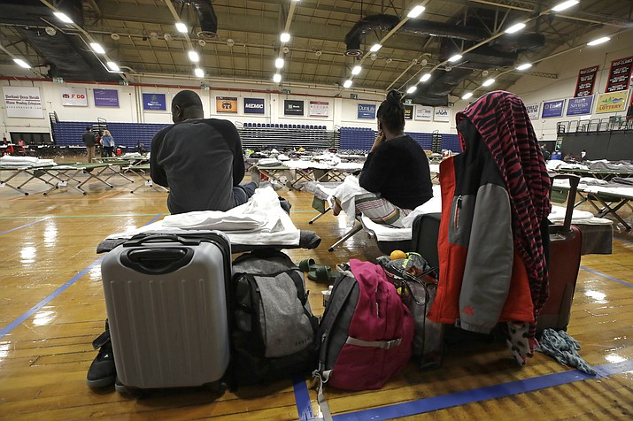 In this June 13, 2019 photo, a migrant couple sit with their belongings inside the Portland Exposition Building in Portland, Maine. Maine's largest city has repurposed the basketball arena as an emergency shelter in anticipation of hundreds of asylum seekers who are headed to the state from the U.S. southern border. Most are arriving from Congo and Angola. (Elise Amendola/AP)