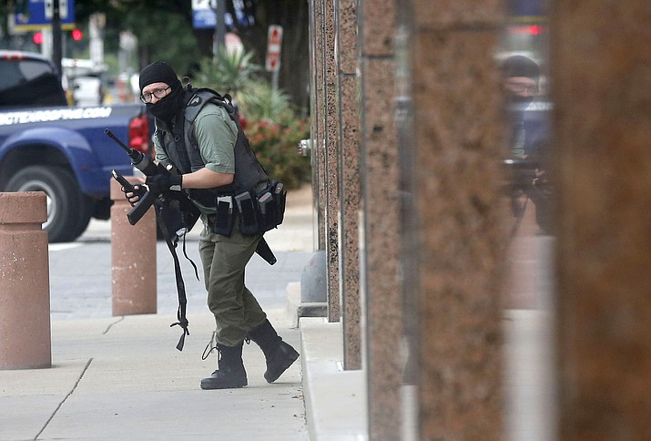 An armed shooter stands near the Earle Cabell Federal Building Monday, June 17, 2019, in downtown Dallas. The shooter was hit and injured in an exchange of gunfire with federal officers outside the courthouse. (Tom Fox/The Dallas Morning News via AP)