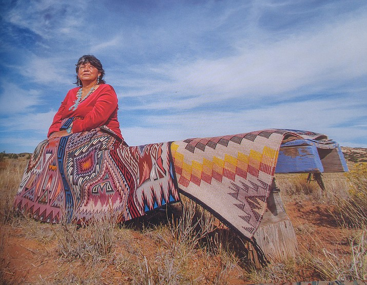 Florence Manygoats is one of the many men and women featured in 'Spider Women's Children: Navajo Weavers Today'. She is from the White Mesa area of Tonalea, Arizona. The striking colors in Florence Manygoats rugs accentuate the colors of her landscape. (Photo by Joe Coca/Thrums Books)