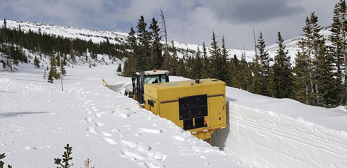 This undated photo provided by the National Park Service shows a snowplow on Trail Ridge Road in Rocky Mountain National Park, Colo., in late April. Heavy winter snow and a cold, wet May in the Rocky Mountains are sending a welcome surge of spring runoff into the rivers of the Southwestern U.S., fending off a water shortage but threatening to push some streams over their banks. (National Park Service via AP)
