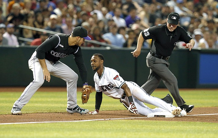 Arizona Diamondbacks' Jarrod Dyson dives safely into third base under the tag of Colorado Rockies third baseman Nolan Arenado, left, on a single hit by Ketel Marte in the fifth inning during a game, Tuesday, June 18, 2019, in Phoenix. (Rick Scuteri/AP)