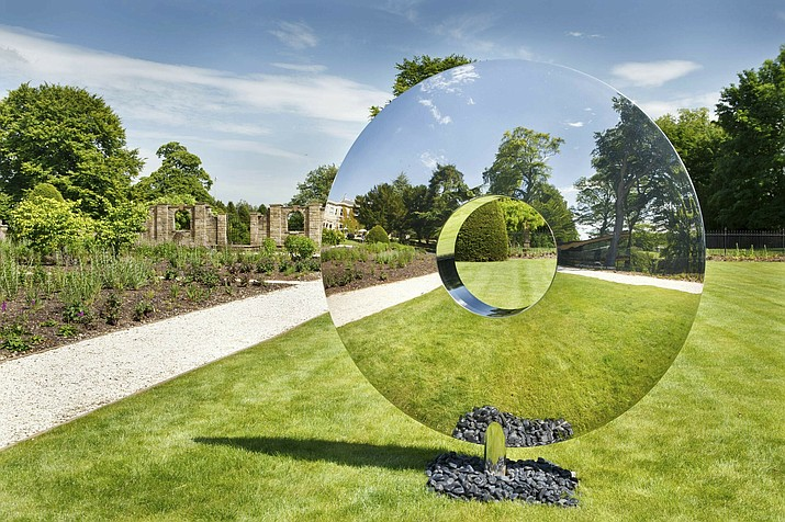 This photo shows British designer David Harber's Torus sculpture. The sculpture is crafted of highly polished steel, and can be made in different sizes. The striking effect: reflections of Torus' surrounding environment grass, trees or water seem to make the piece transparent. (Clive Nichols/David Harber via AP)