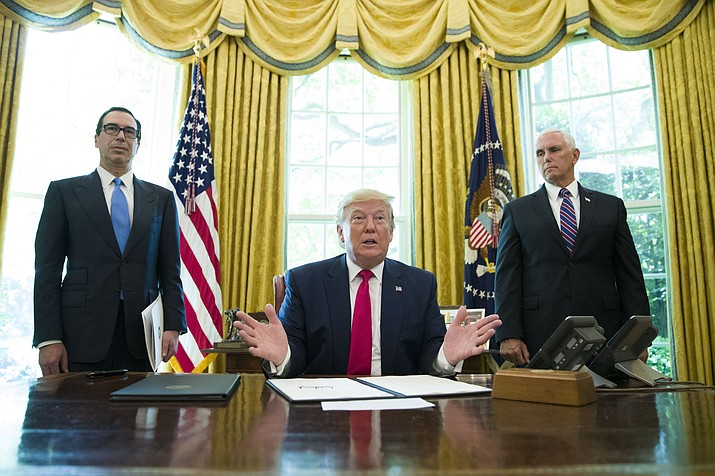 President Donald Trump listens to a reporter's question after signing an executive order to increase sanctions on Iran, in the Oval Office of the White House, Monday, June 24, 2019, in Washington. Trump is accompanied by Treasury Secretary Steve Mnuchin, left, and Vice President Mike Pence. (Alex Brandon/AP)