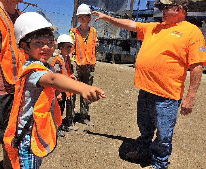 "James Tartaglia, 6, left reacts to machinery moving trash from a large pile into the blades of the ""breaker"" while touring the Patriot Disposal recycling facility June 21. Bob Blakenship, right, with Patriot, helped lead the tour that also included Kristina Bjerknes, center, and her children, Luke, 8, and Adela, 11, (not visible). (Sue Tone/Tribune)"