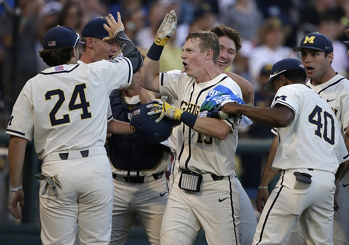 Michigan's Jimmy Kerr, center, is congratulated after hitting a 2-run home run against Vanderbilt during the seventh inning in Game 1 of the NCAA College World Series baseball finals in Omaha, Neb., Monday, June 24, 2019. (Nati Harnik/AP)
