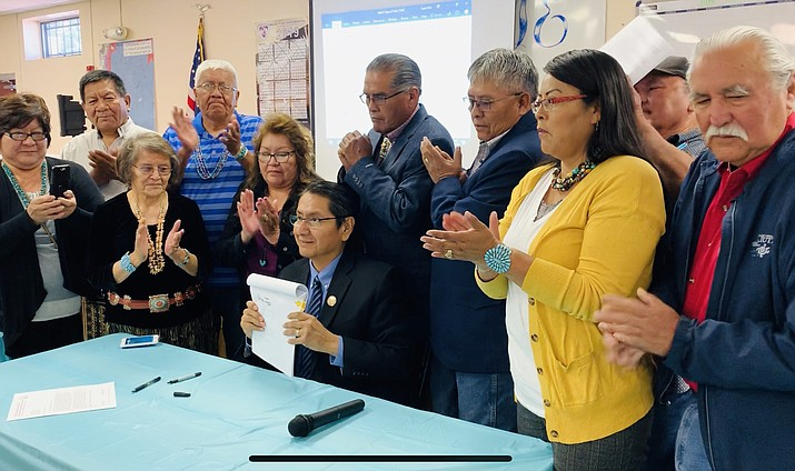 Navajo Nation President Jonathan Nez holds up Resolution CJN-22-19 allowing stipend and works compensation funding for 110 of the Nation's chapters officials. (Photo/OPVP)