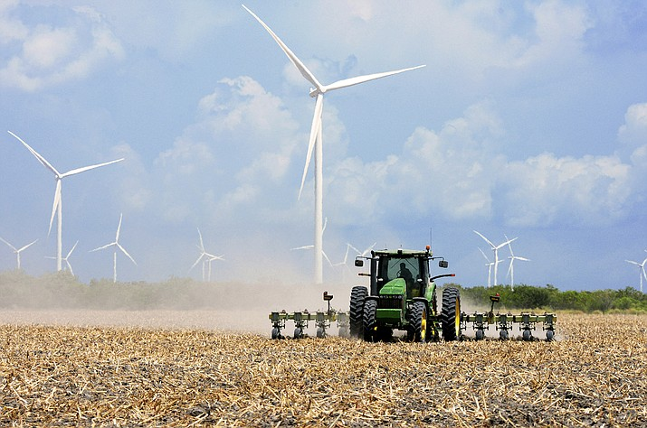 A 2015 file photo shows a farmer plowing his recently harvested field under wind turbines in the agricultural area north of Rio Hondo, Texas, near the New Mexico border. A new wind farm is coming to southeast New Mexico, and the project will bring turbines and transmission lines to key counties, the San Diego-based EDF Renewables recently announced. (Jason Hoekema/Valley Morning Star via AP, File)