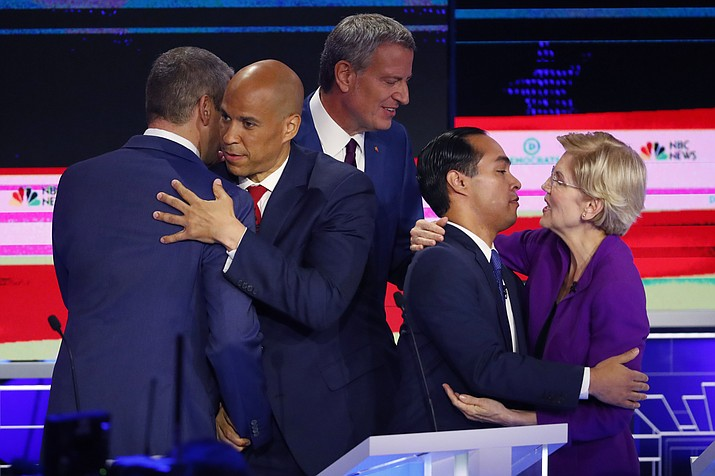 Democratic presidential candidate Sen. Cory Booker, D-N.J., second from left, hugs Rep. Tim Ryan, D-Ohio, while Sen. Elizabeth Warren, D-Mass., hugs former Housing and Urban Development Secretary Julian Castro at the end of a Democratic primary debate hosted by NBC News at the Adrienne Arsht Center for the Performing Arts, Wednesday, June 26, 2019, in Miami. In between them is New York City Mayor Bill de Blasio. (Wilfredo Lee/AP)