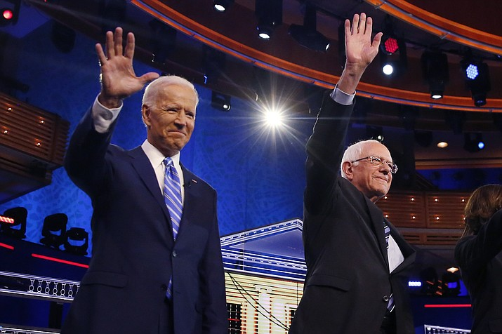 Democratic presidential candidates former vice president Joe Biden, left, and Sen. Bernie Sanders, I-Vt., wave before the start of a Democratic primary debate hosted by NBC News at the Adrienne Arsht Center for the Performing Arts, Thursday, June 27, 2019, in Miami. (Brynn Anderson/AP)