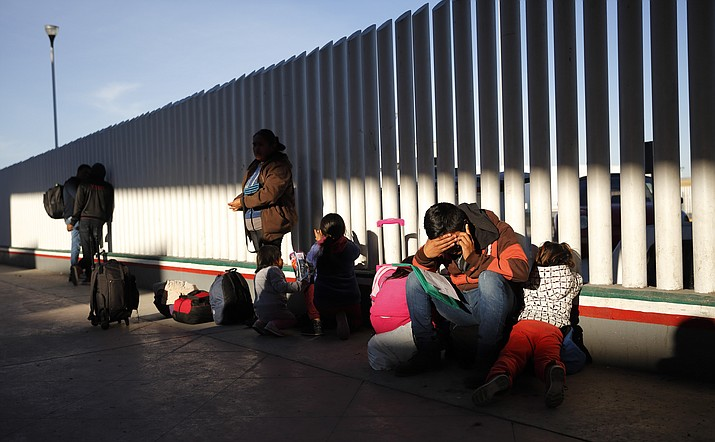 In this Jan. 25, 2019, file photo, a migrant sits with his children as they wait to hear if their number is called to apply for asylum in the United States, at the border in Tijuana, Mexico. Migrants who are being forced to wait in Mexico while they try to win asylum in the U.S. complain they are being subjected to violence in border cities. (Gregory Bull/AP, file)