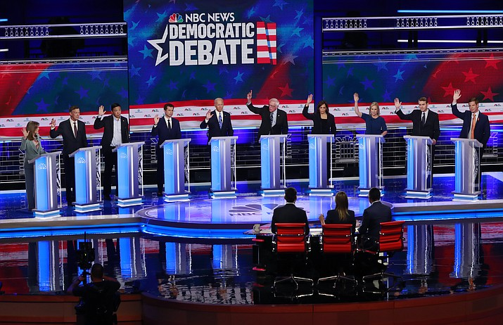 Democratic presidential candidates, author Marianne Williamson, former Colorado Gov. John Hickenlooper, entrepreneur Andrew Yang, South Bend Mayor Pete Buttigieg, former Vice President Joe Biden, Sen. Bernie Sanders, I-Vt., Sen. Kamala Harris, D-Calif., Sen. Kirsten Gillibrand, D-N.Y., former Colorado Sen. Michael Bennet, and Rep. Eric Swalwell, D-Calif., raise their hands when asked if they would provide healthcare for undocumented immigrants, during the Democratic primary debate hosted by NBC News at the Adrienne Arsht Center for the Performing Arts, Thursday, June 27, 2019, in Miami. (Wilfredo Lee/AP)