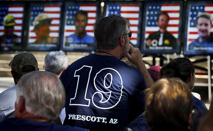 People listen as the 19 Granite Mountain Hotshots are memorialized on the first anniversary of their deaths, June 30, 2014, during a ceremony outside the Yavapai County courthouse in Prescott, Arizona. (AP Photo/Matt York)