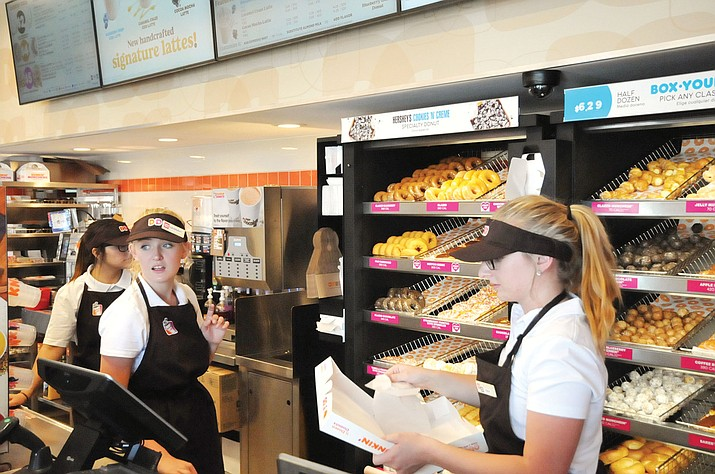 Cashiers Faith Kloster of Prescott, right, and Hannah Robertson of Prescott Valley help customers pick out their doughnuts during the soft opening of the new Dunkin'/Baskin-Robbins store in Prescott Valley June 25. (Doug Cook/Courier)
