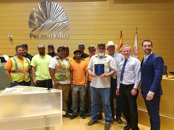 Bruce Handley, holding a plaque, was honored at the June 27, 2019, Town Council meeting. He retired after 30 years with the Town of Prescott Valley's Public Works Department. (Sue Tone/Tribune)