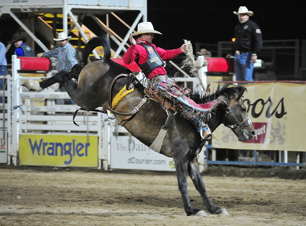 CoBurn Bradshaw scores 84 on Joker for the lead in the saddle bronc riding during the first performance of the Prescott Frontier Days Rodeo Monday July 1, 2019.  (Les Stukenberg/Courier)