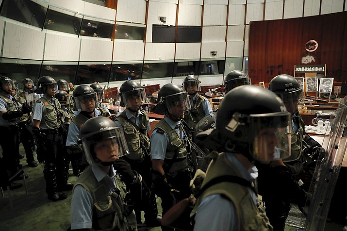 Police officers with protective gear retake the meeting hall of the Legislative Council in Hong Kong, during the early hours of Tuesday, July 2, 2019. Hundreds of protesters in Hong Kong swarmed into the legislature's main building Monday night, tearing down portraits of legislative leaders and spray-painting pro-democracy slogans on the walls of the main chamber as frustration over a lack of response from the administration to opposition demands boiled over. (Kin Cheung/AP)