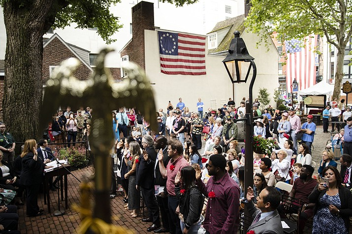 Immigrants raise their right hands and take the oath of citizenship of the United States at the Betsy Ross House in Philadelphia, during a naturalization ceremony on Flag Day, Friday, June 14, 2019. (Matt Rourke/AP)